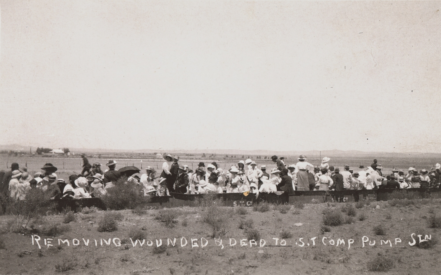 Line of people in outback setting on train line.