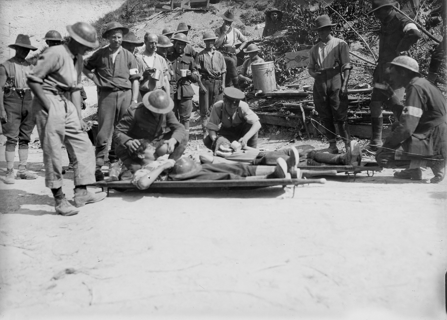 Men tending to injured soldiers lying on stretchers on ground outdoors.