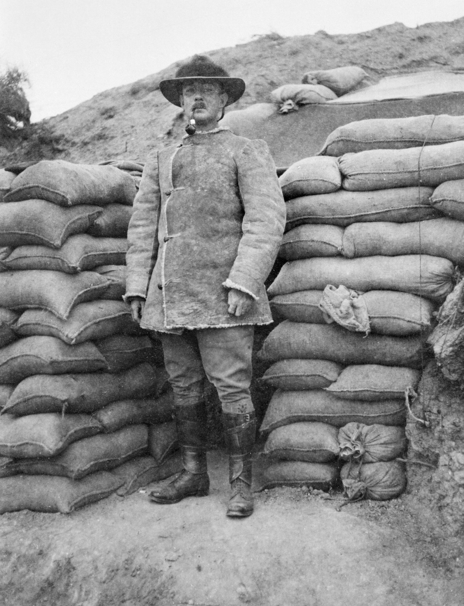 Black and white photo of man in front of sandbags.