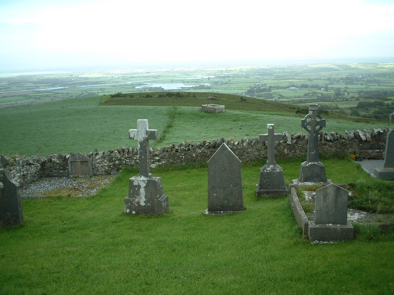 Misty green fields and freestone fences with gravestones in the foreground and sweeping pastures in the backround with sea in the distance.
