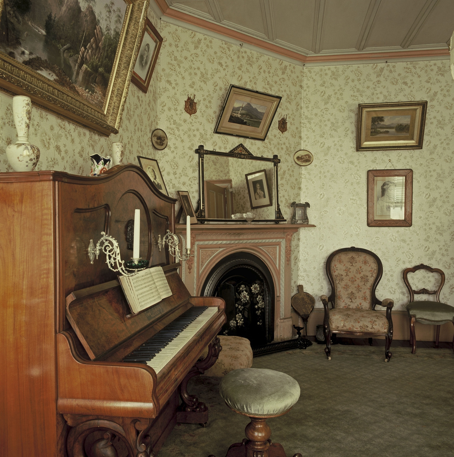 Colour photo of room with piano, fireplace, chairs, ornaments and frame pictures on wallpapered walls.