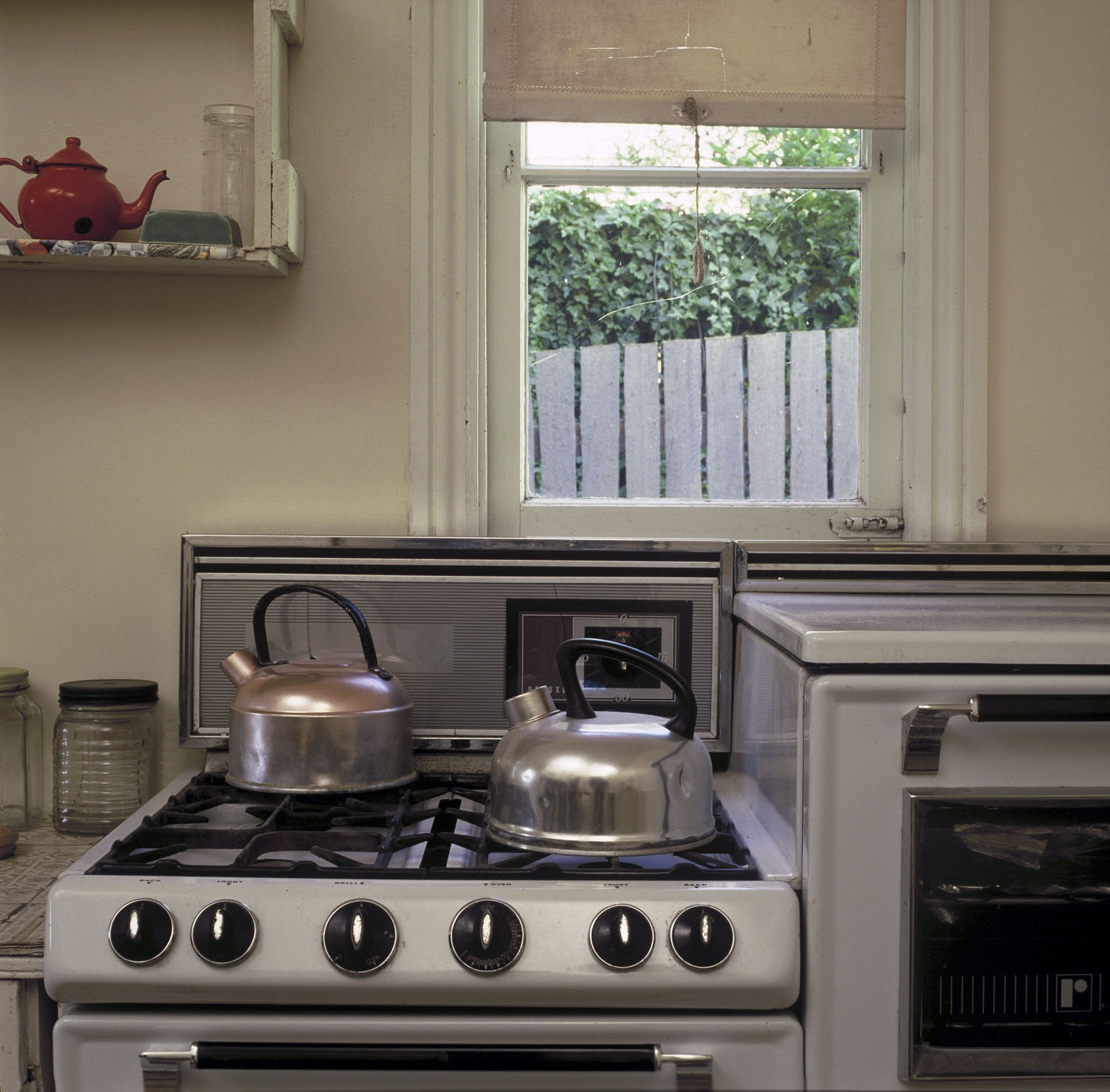 Image of the kitchen ant Meroogal. The oven is taking up the lower right of the frame, and the window the upper left. A kettle is sitting on the oven.