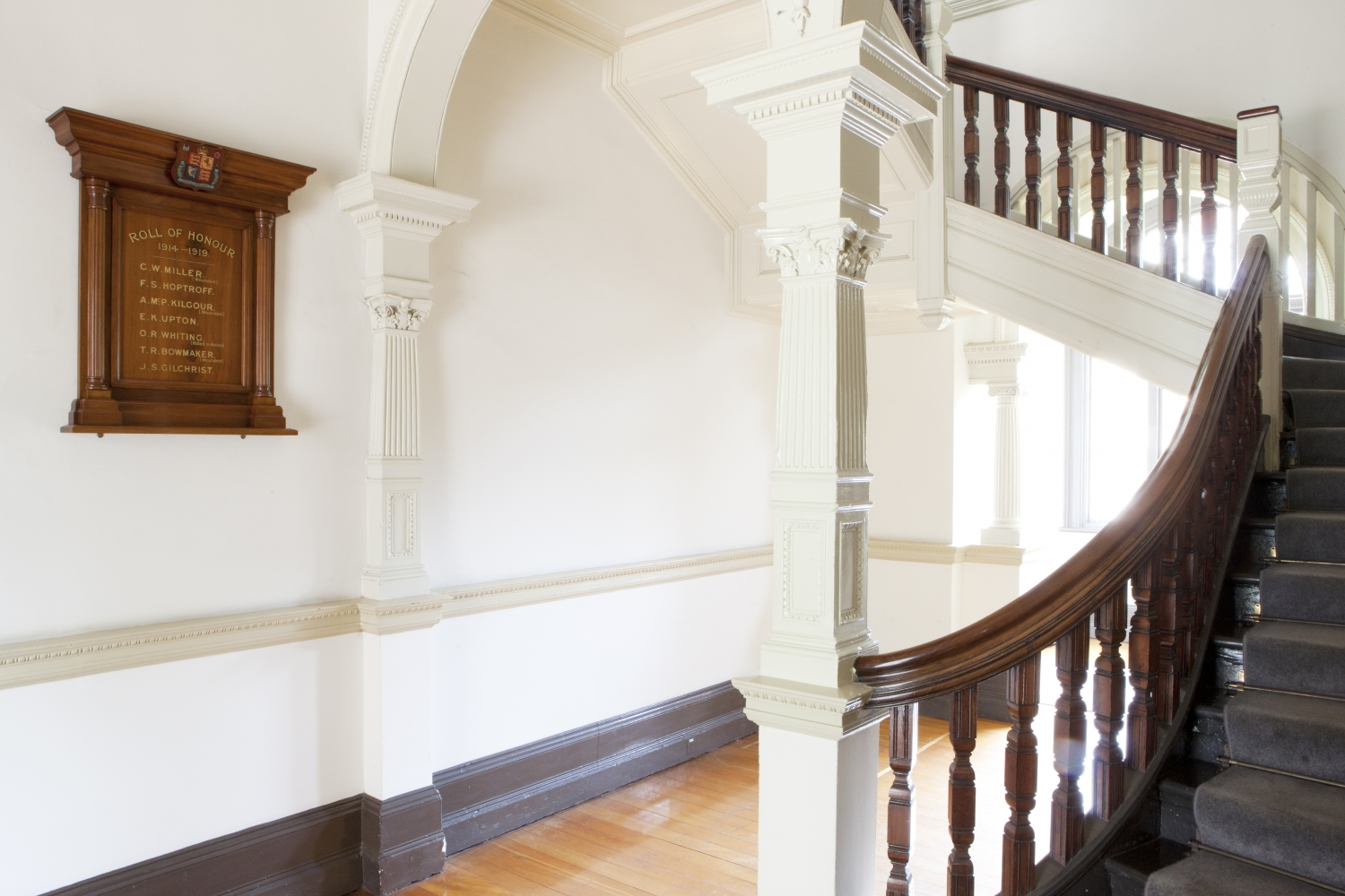 Wooden honour roll on wall with curved staircase to right.