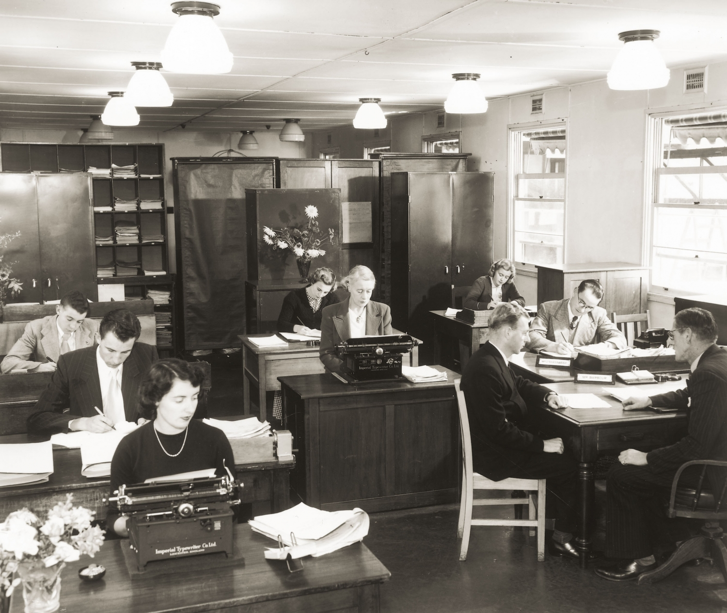 Office with several women on typewriters and men working at desks on paperwork. The room is filled with heavy office furniture, low ceiling and rows of lights.