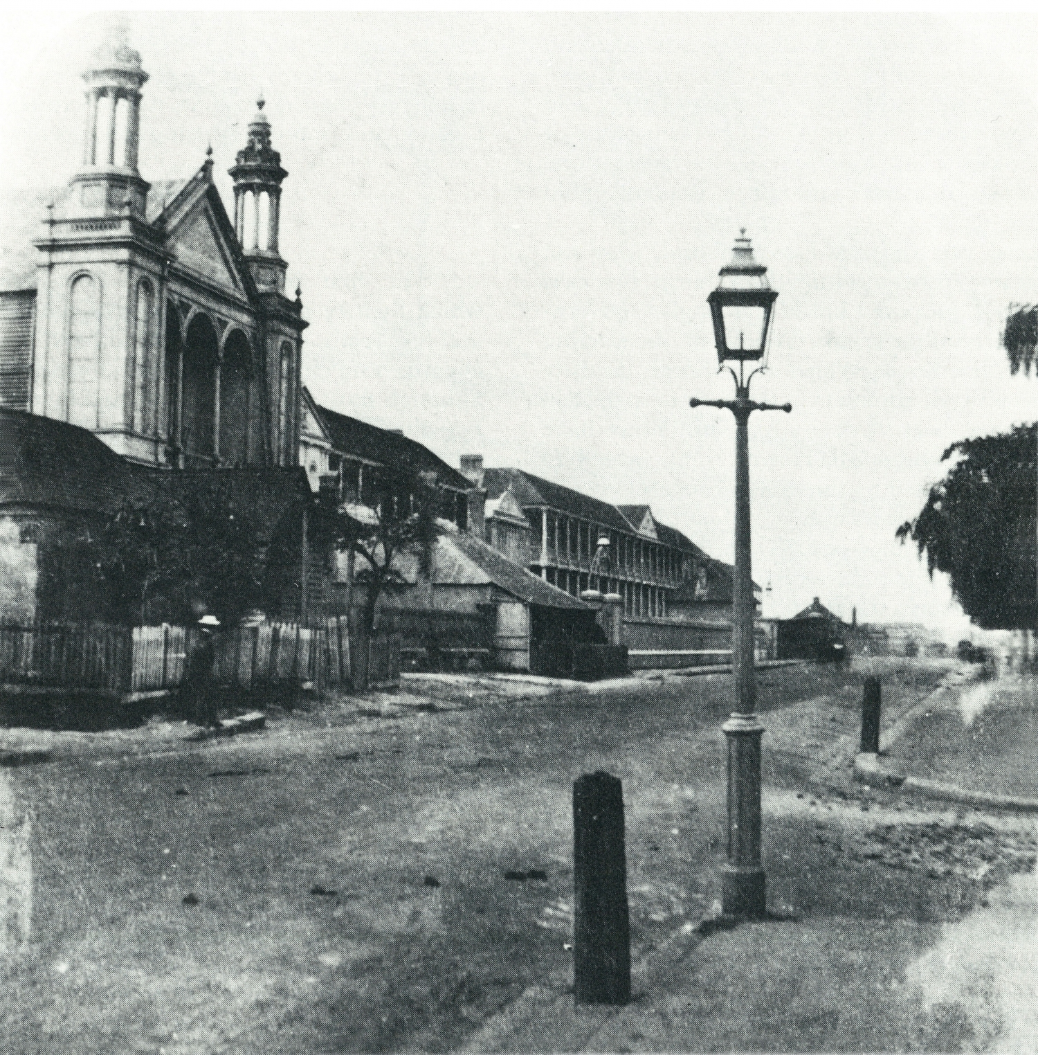 B/W photo of city street with large buildings, including a church lining one side and a footpath and street light on the opposite side.