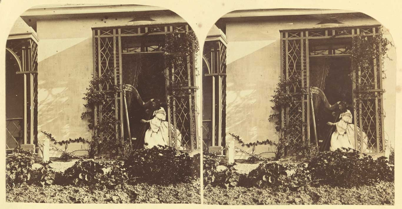 Sepia toned photo of view of woman seated in window with harp, framed by treillage lattice work.