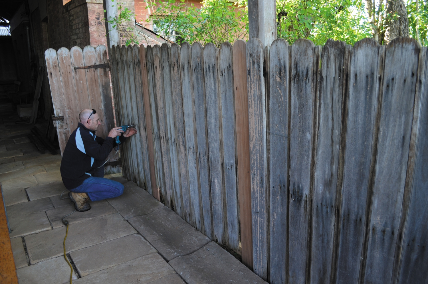 Man in blue pants and black shirt with power drill crouches in front of wooden fence