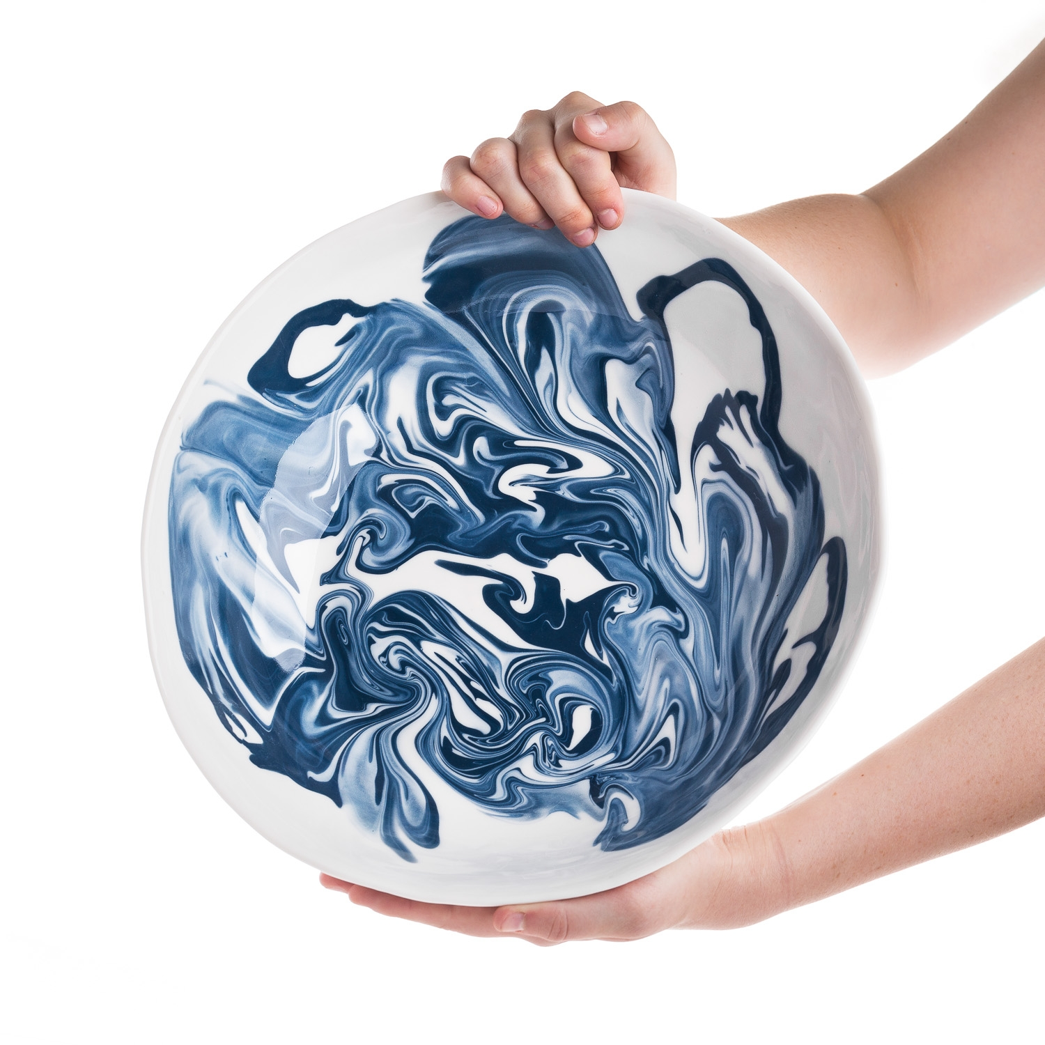 Hands holding large decorated plate with blue design on white background.