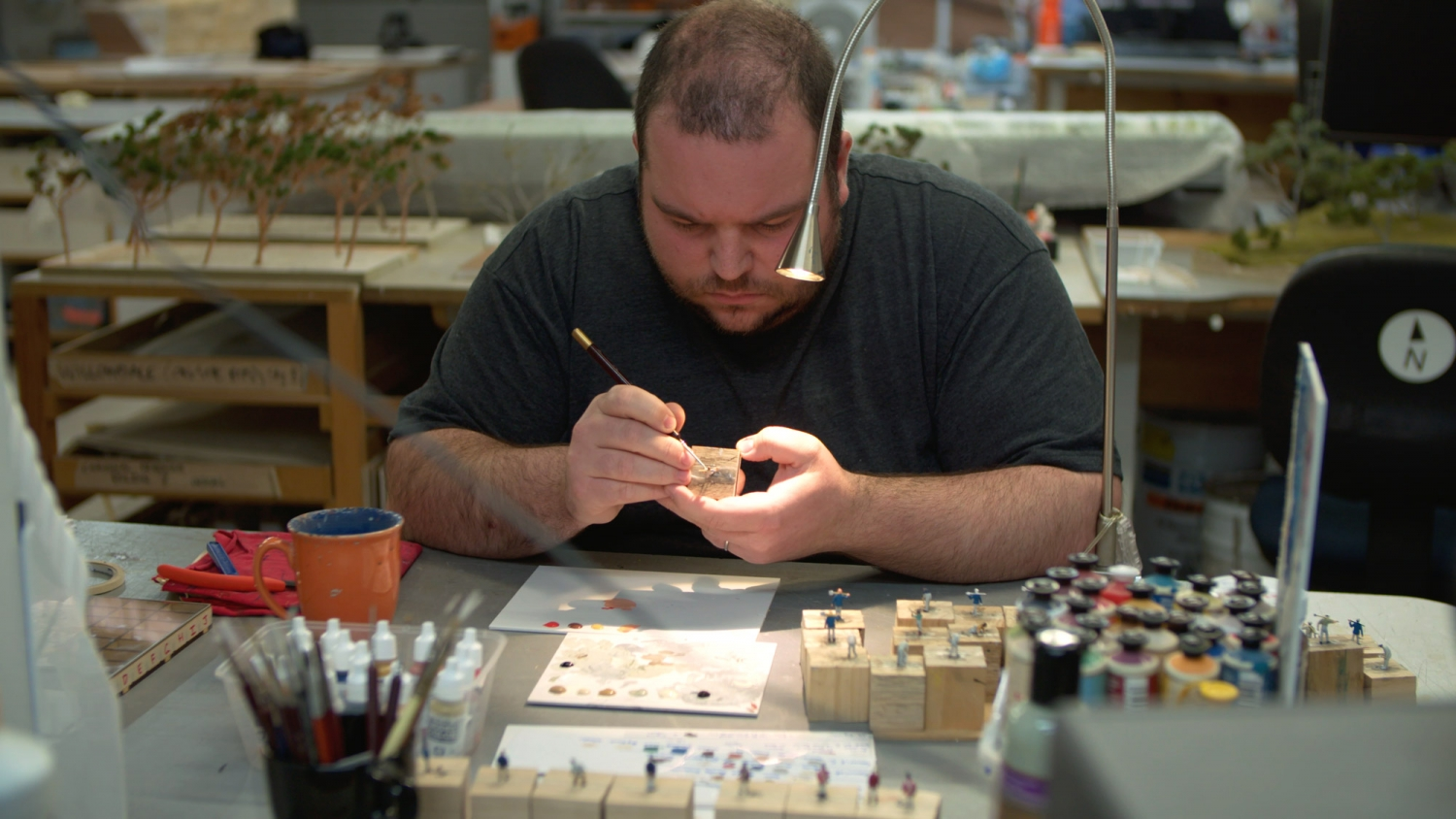 Man working on model with equipment on desk in front of him.