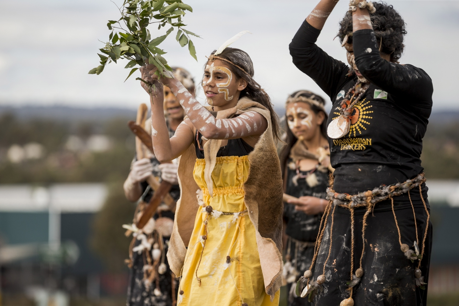 Indigenous dancers with leaves, central figure in yellow dress.