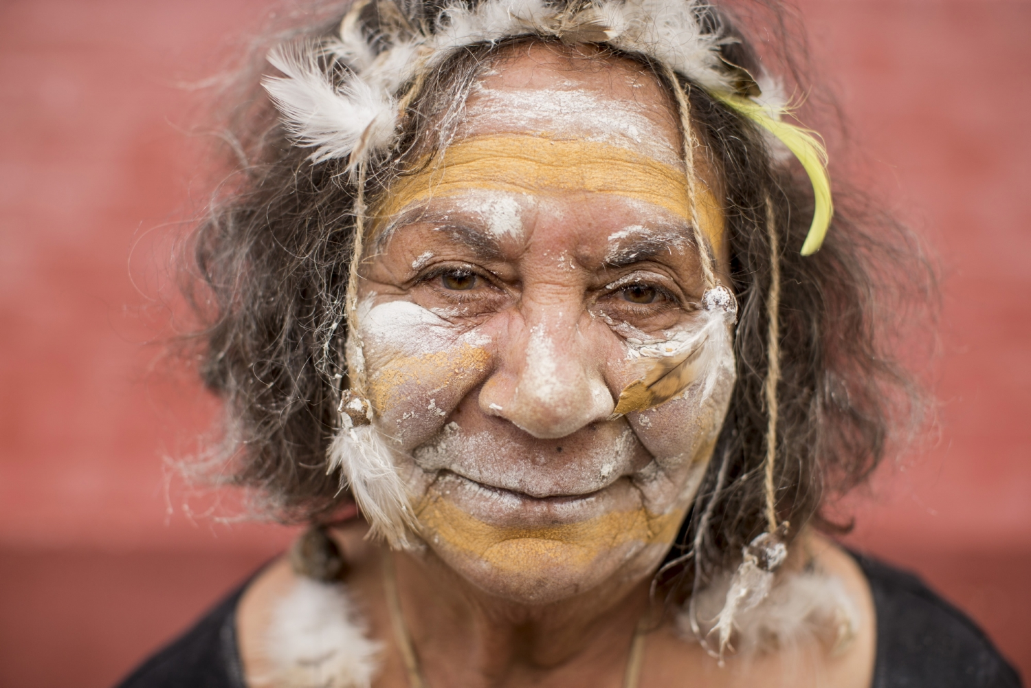 Older indigenous woman with face paint and feather hair adornments.