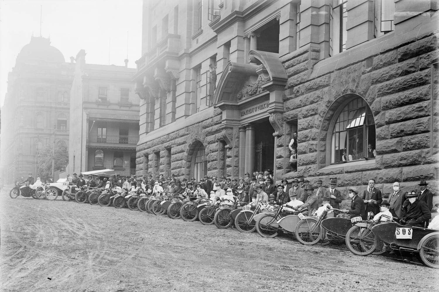 Row of motorbikes and their riders, some in masks, in front of imposing sandstone building. Black and white photo.