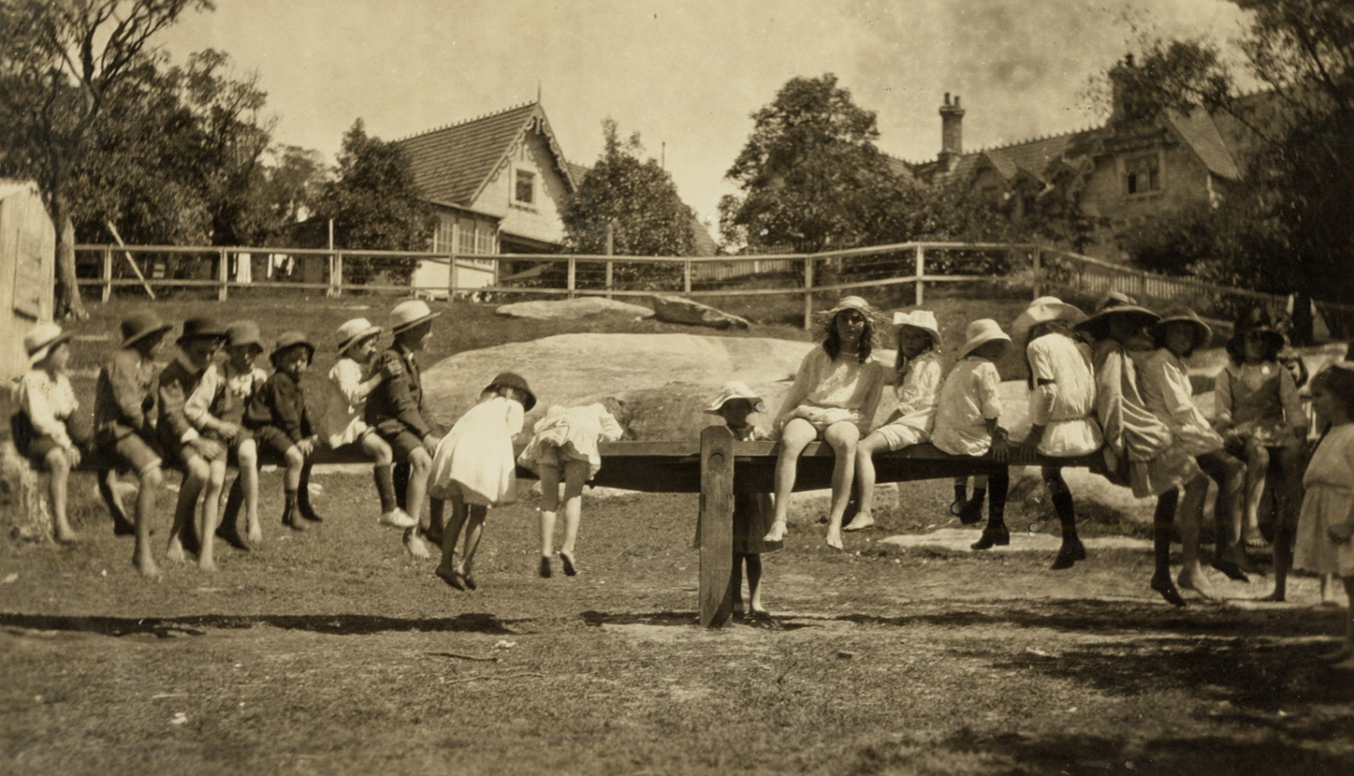 Black and white photograph of children on a seesaw