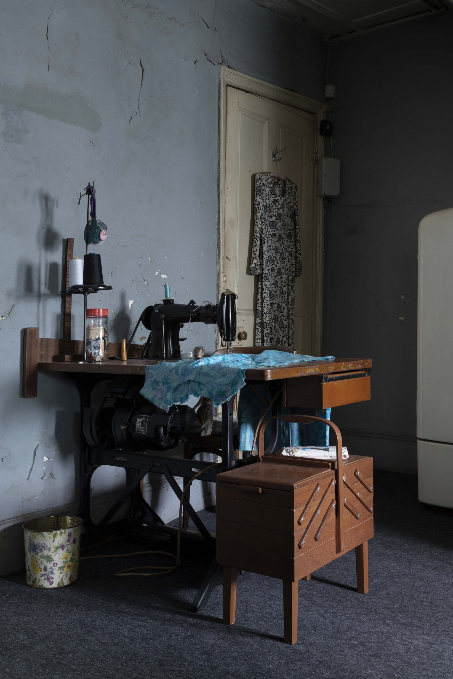 Sewing machine with assorted boxes, garments and floral bin, with dress hanging from door in background.