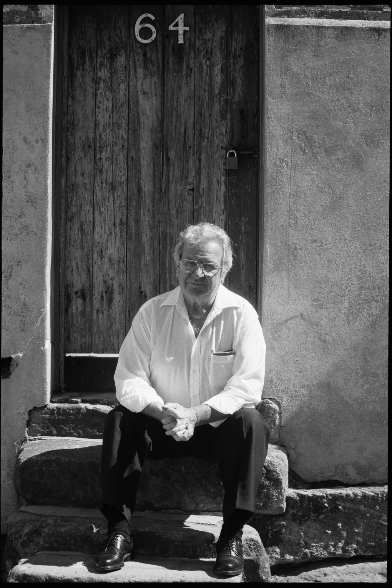 Black and white photo of man seated on step.
