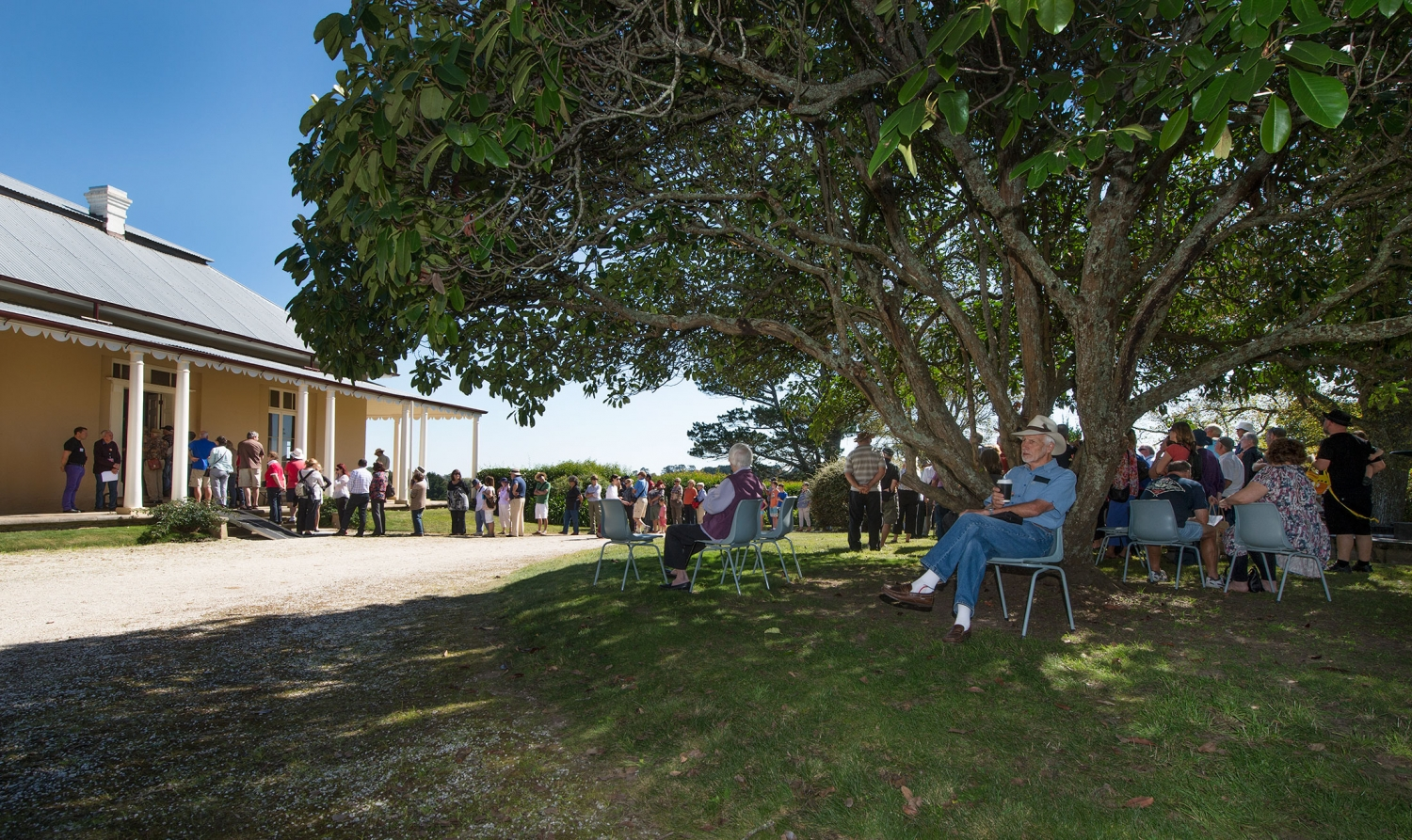 Colour photo of historic house with wide verandahs with visitors sitting on chairs under a large tree and inspecting the grounds.