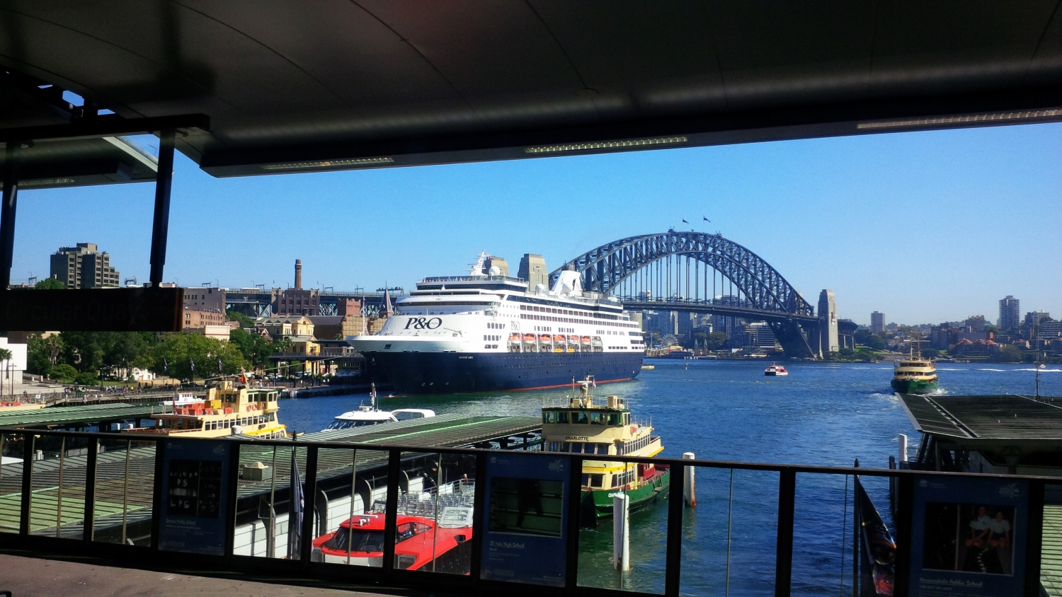 Large ocean liner with dark blue hull alongside passenger terminal at circular quay, Sydney Harbour with the Sydney Harbour Bridge in the background and ferry terminals in the foreground