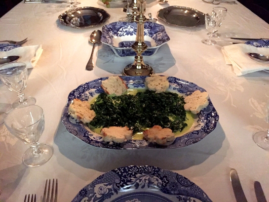 Blue and white platter with spinach dish surrounded by flower shaped croutons.