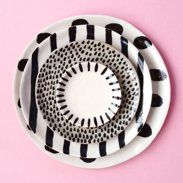 Stack of three differently sized plates in varied black and white patterns.