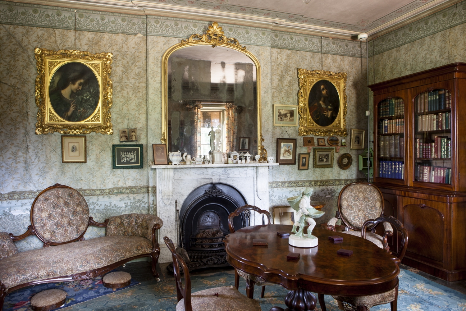 Ornately furnished room with paintings on walls above fireplace.