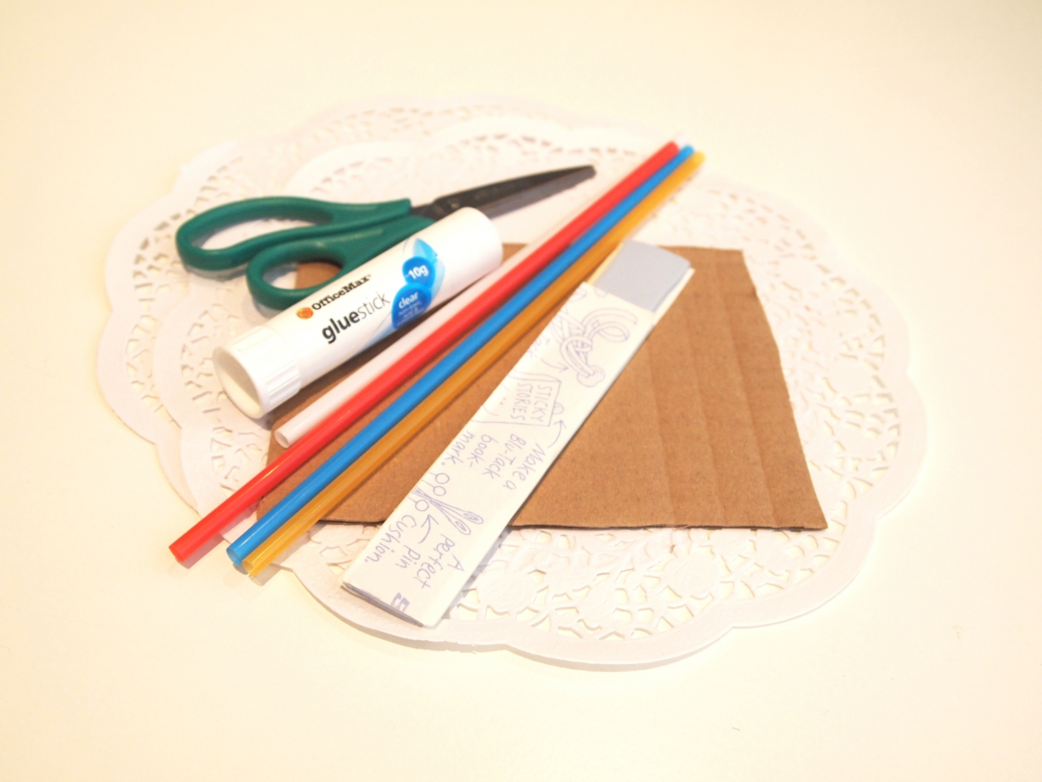Selection of craft resources: Cardboard, scissors, a straw, blu-tac, glue and a mini doily.