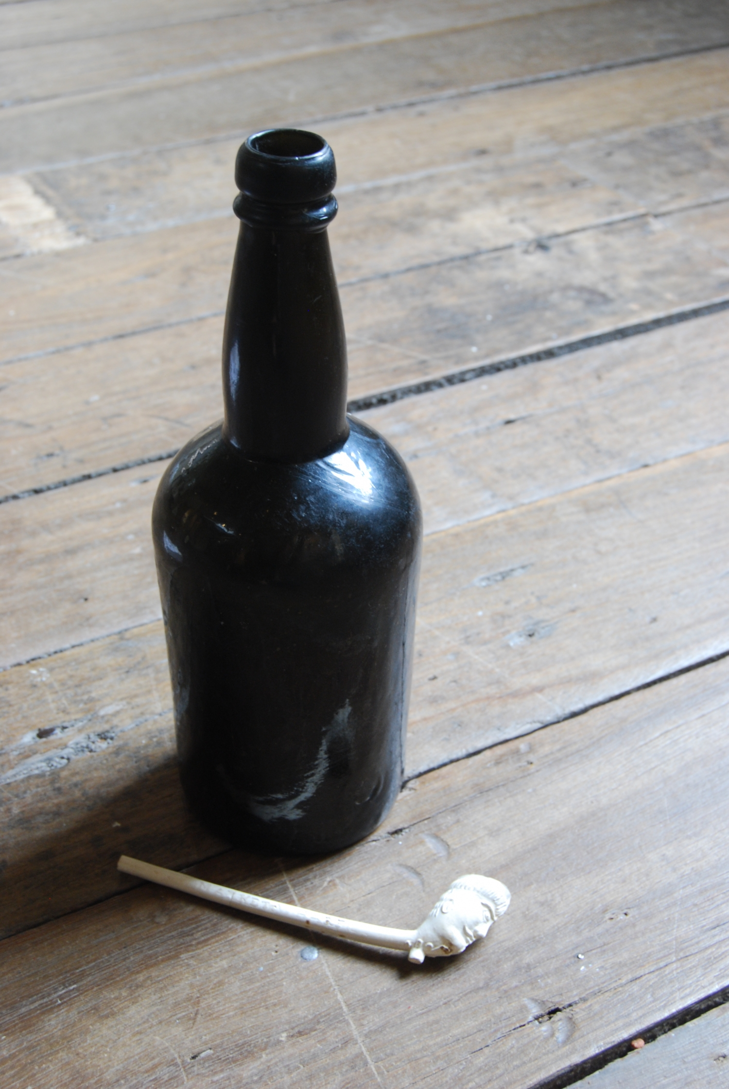 Brown glass bottle and carved bone pipe.