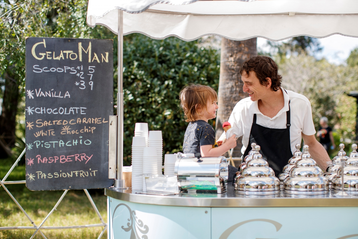 Man and child with old fashioned icecream cart in outdoor setting.