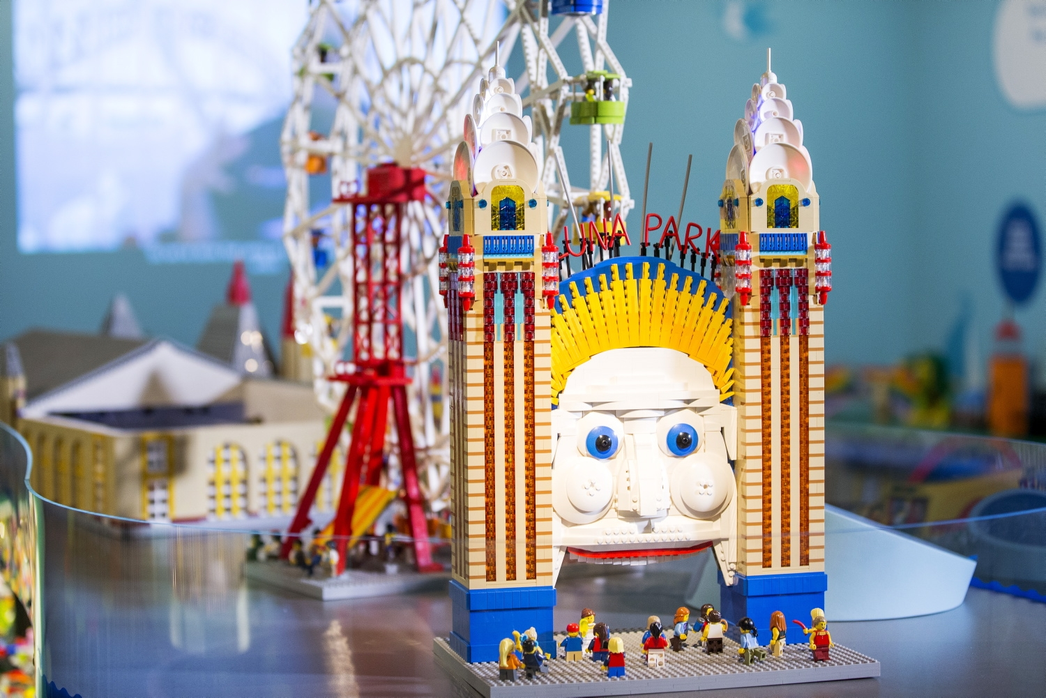 Exhibition table of bright and colourful lego models of Luna Park, including entrance face, ferris wheel, medieval-like crystal place and roller coaster
