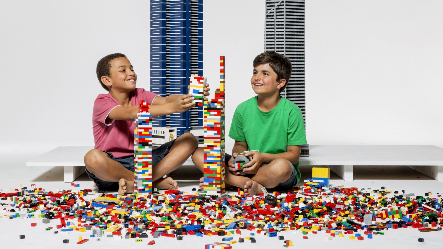 two young boys playing with colourful LEGO in front of large LEGO towers against a white background