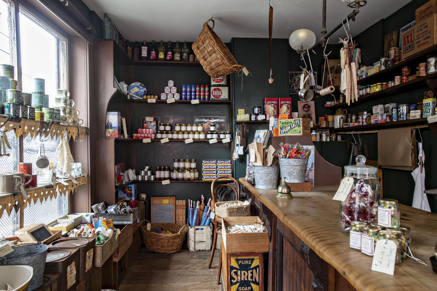Old-fashioned shop interiro with long bench to right and shelving to right and back, carrying a variety of jars and packets, with objects hanging from hooks over the counter.