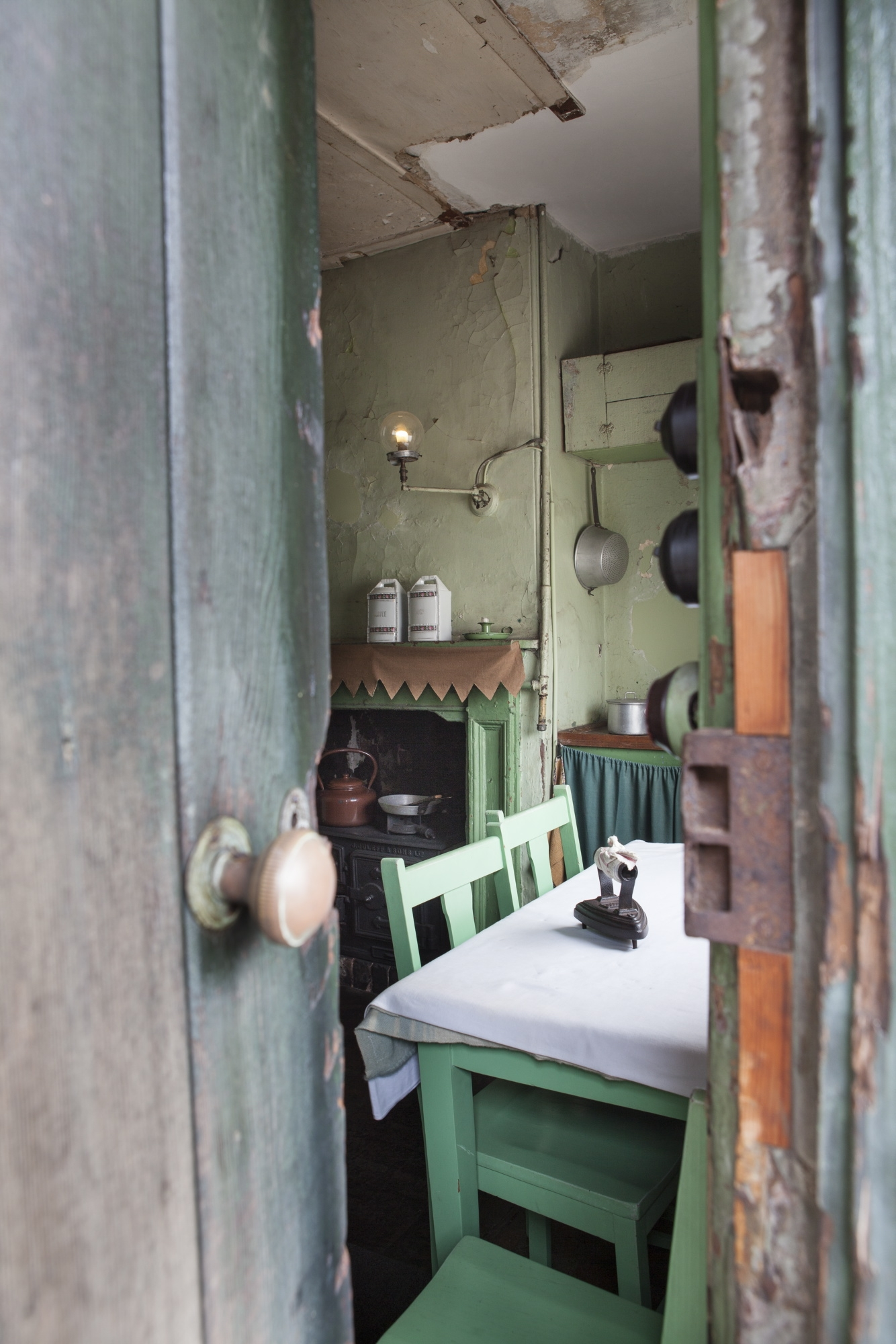 Looking through doorway at table with white tablecloth and old fashioned iron on top, with pale green chairs behind and view of fireplace with light fitting above.