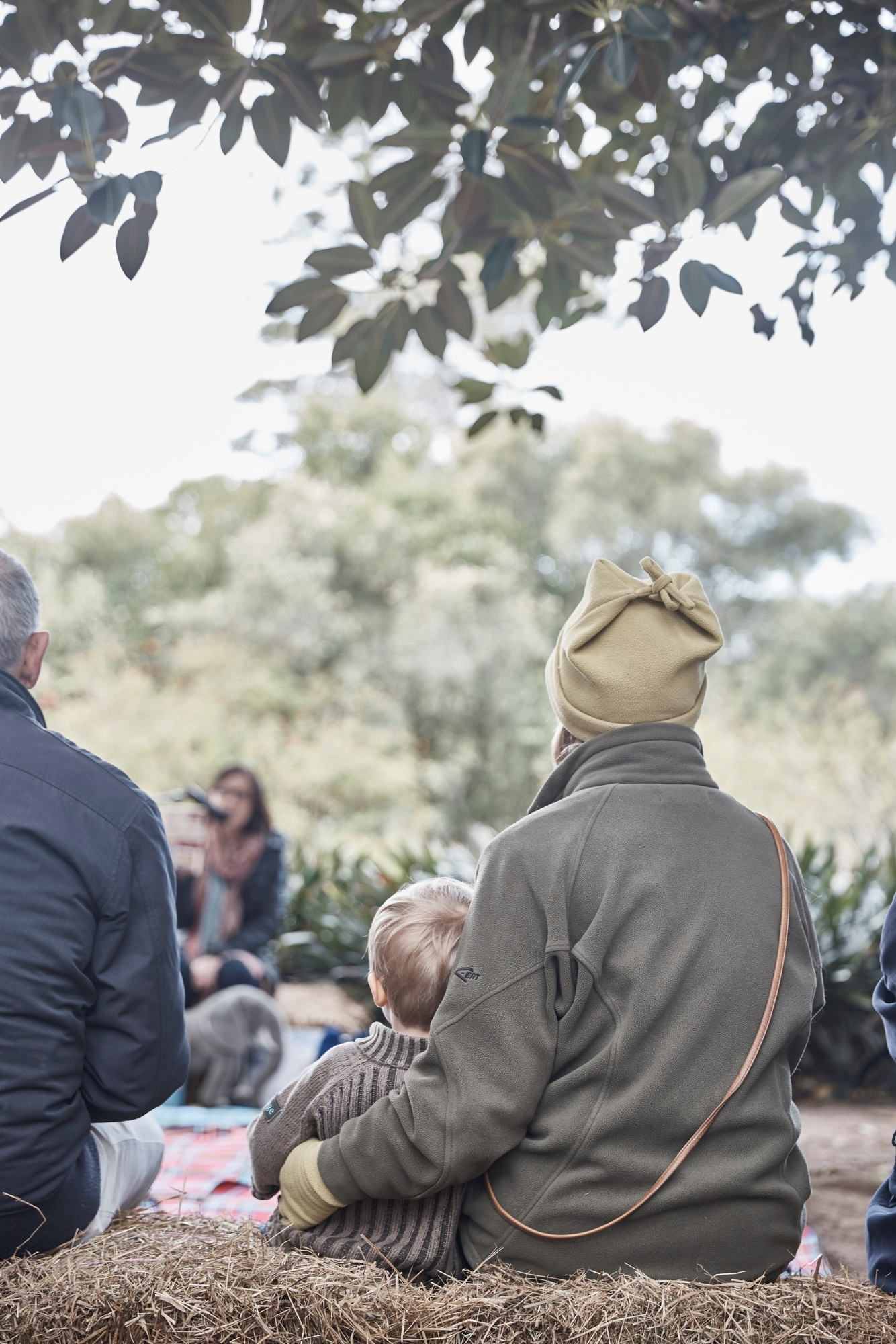 People seated on rugs under tree in outdoor setting.