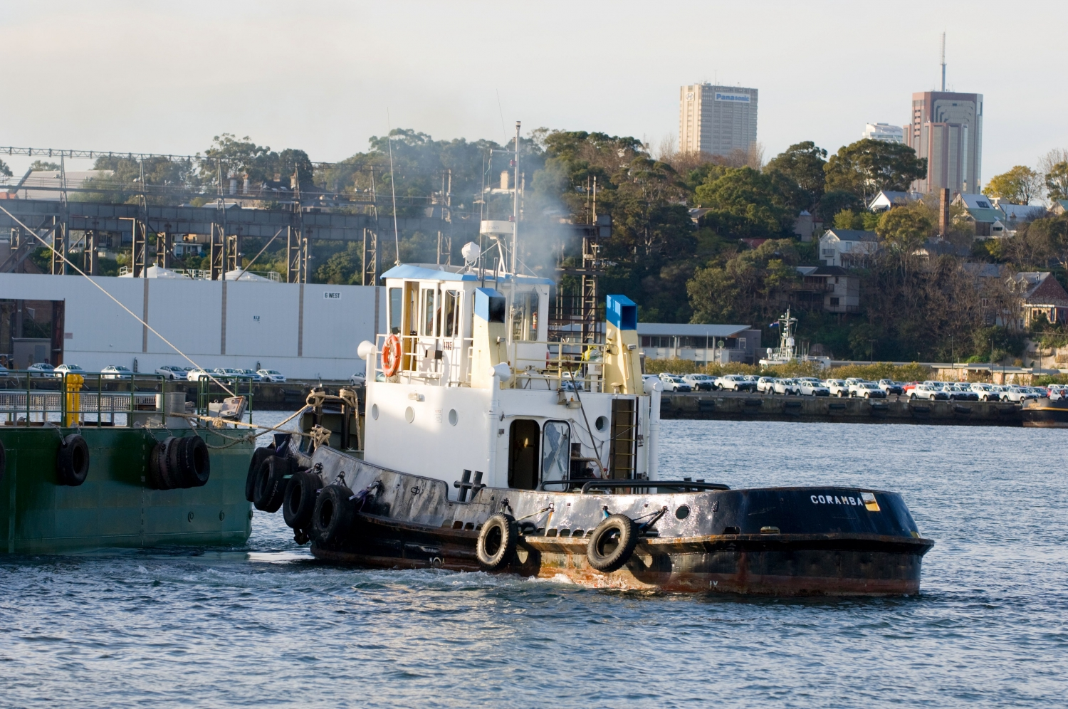 Small tugboat with cabin and tyre bumpers in Sydney Harbour.