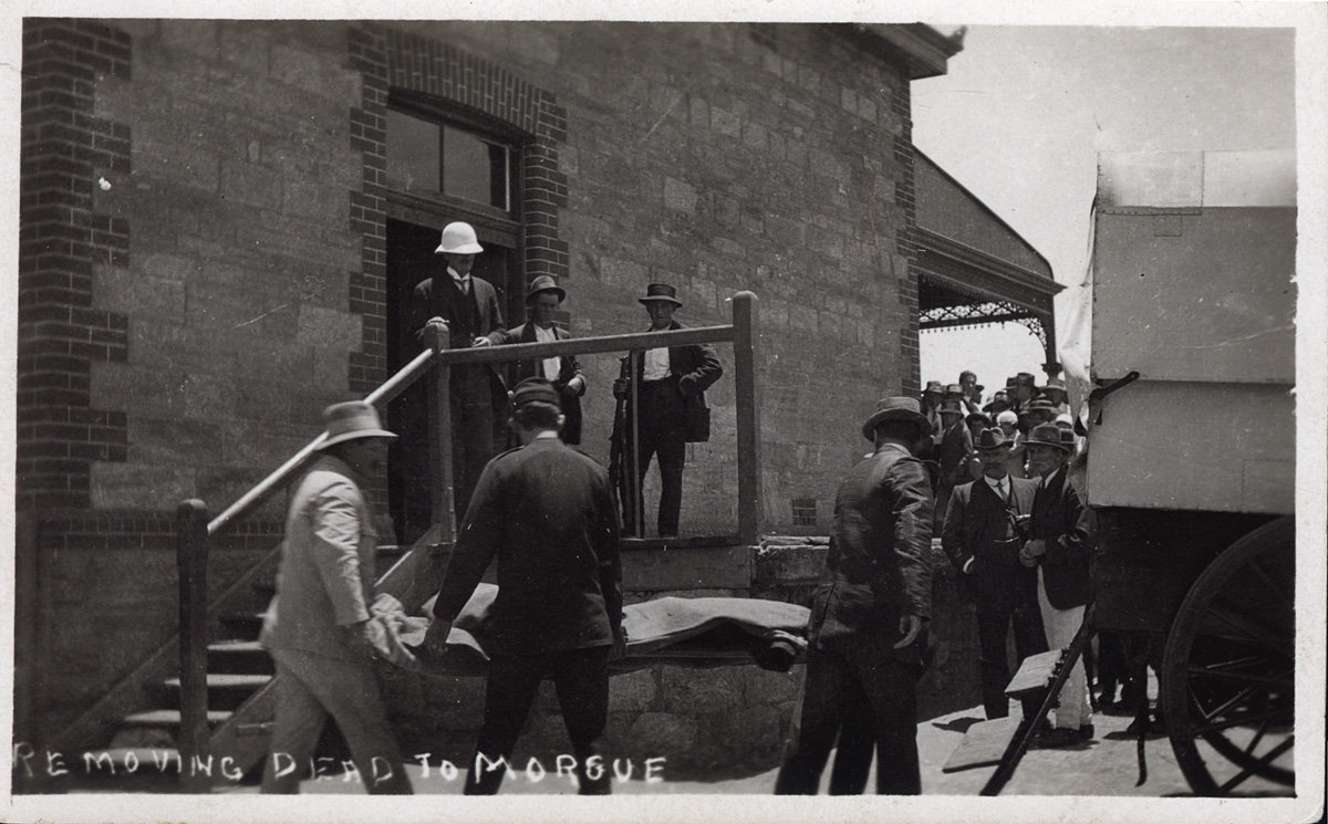 Men carrying covered stretcher to staircase of stone building with onlookers in background.