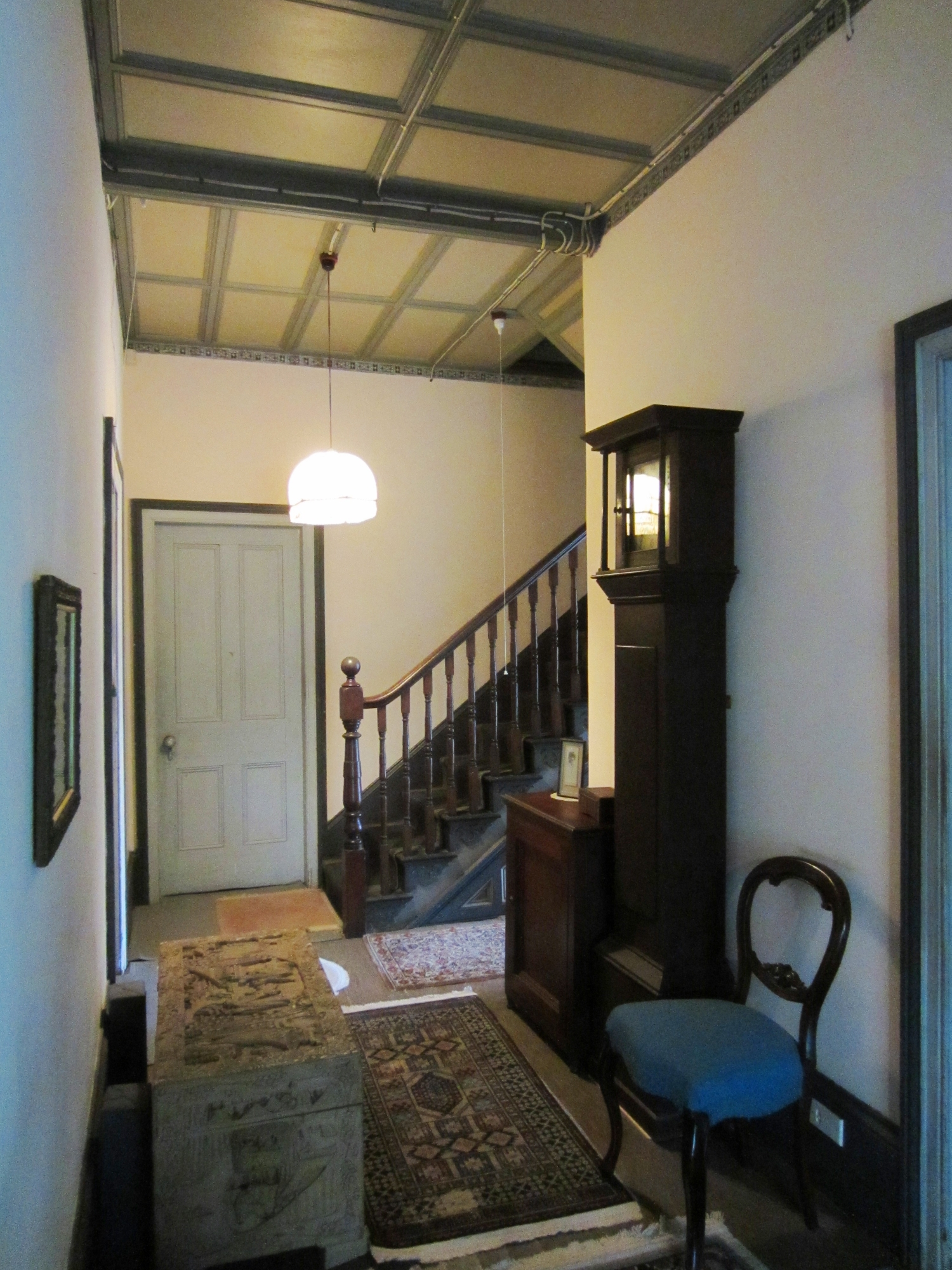 View down hallway towards stairs with clock on righthand side in middle ground.