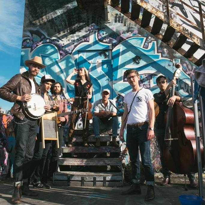 Group of musicians in shed with gridlike shadows behind them.