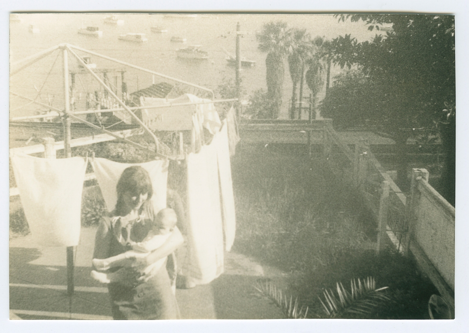 Black and white photo of woman holding baby in front of clothes line.