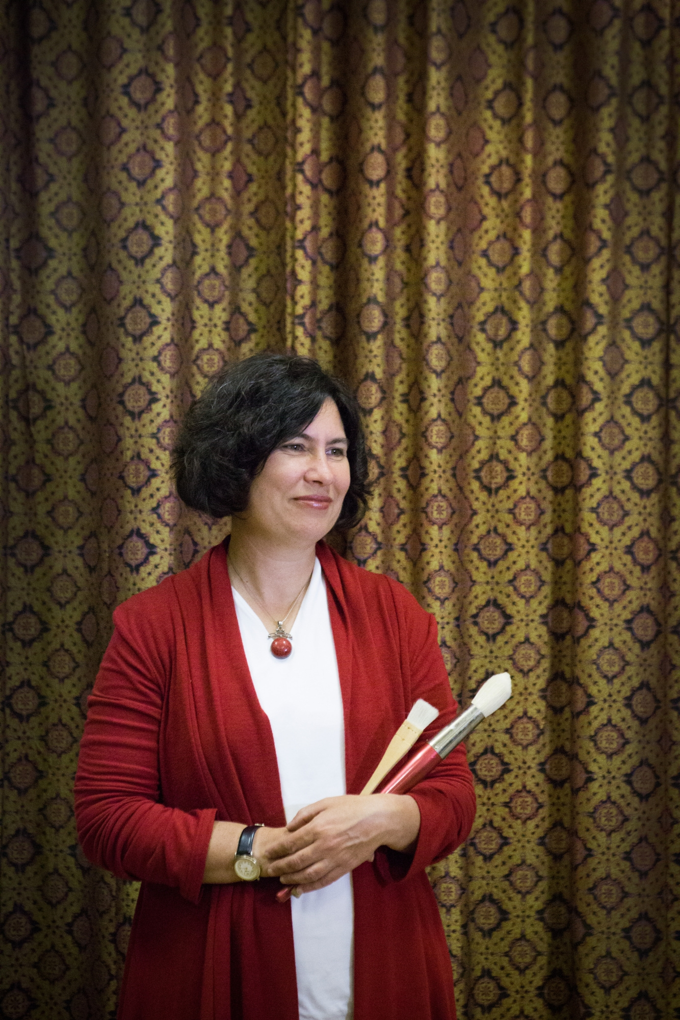 Woman in red cardigan and white top in front of patterned fabric, holding brushes.