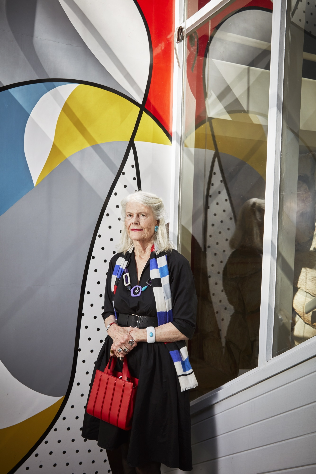 Woman standing in front of colourful modernist mural.