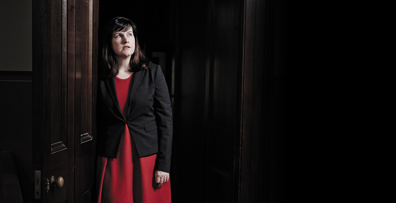 Dark haired woman wearing a red dress and black blazer leaning on a wooden door frame
