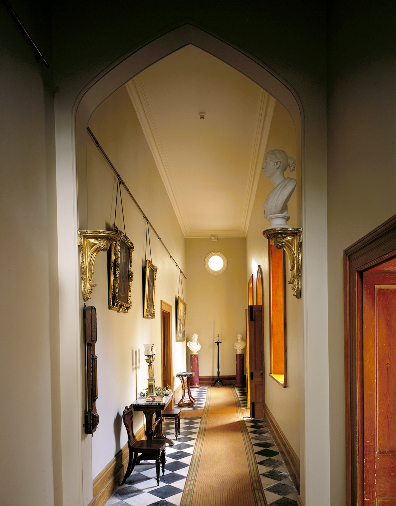 Portrait image of the hallway in Vaucluse House. A black and white tiled floor sits under a number of busts on stands.