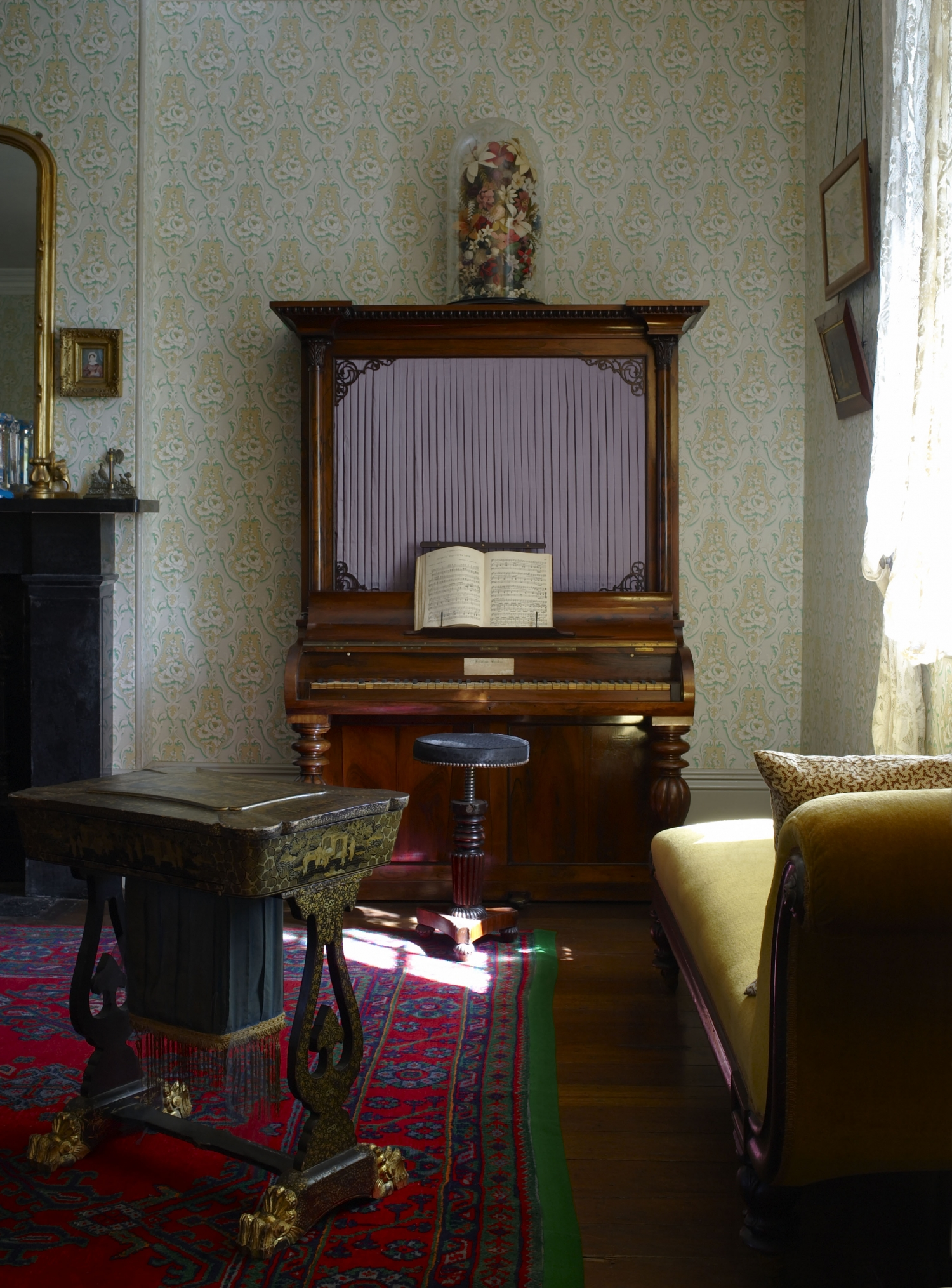 Colour photo of room at Vaucluse House showing couch, piano and sewing box on red and blue carpet.