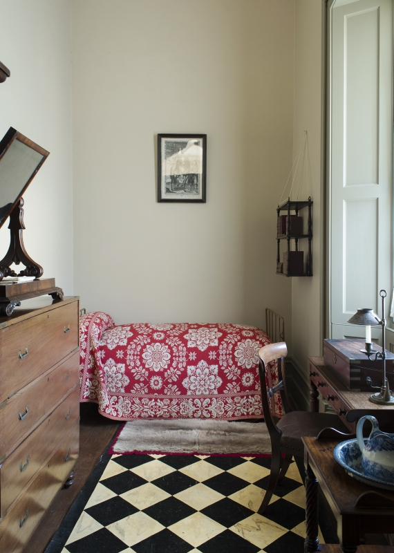 Interior of small narrow room with bed at end coveredwith colourful floral spread and window to right.