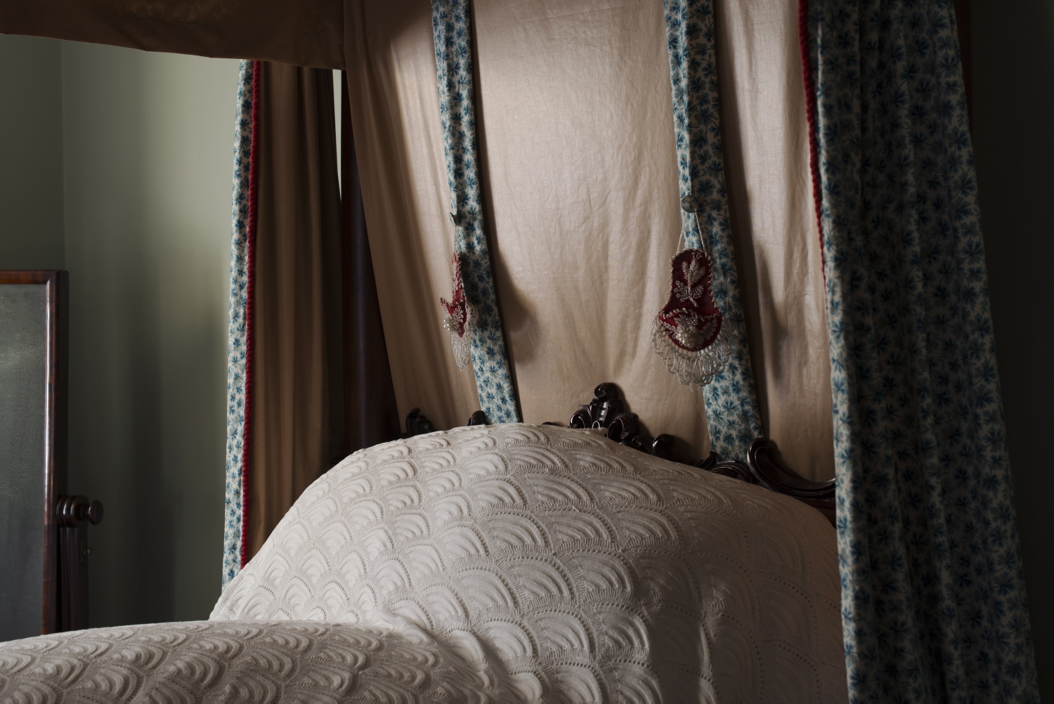 Head of bed showing the watch pocket of red plush fabric and decorated with glass and pearl beads in floral patterns.