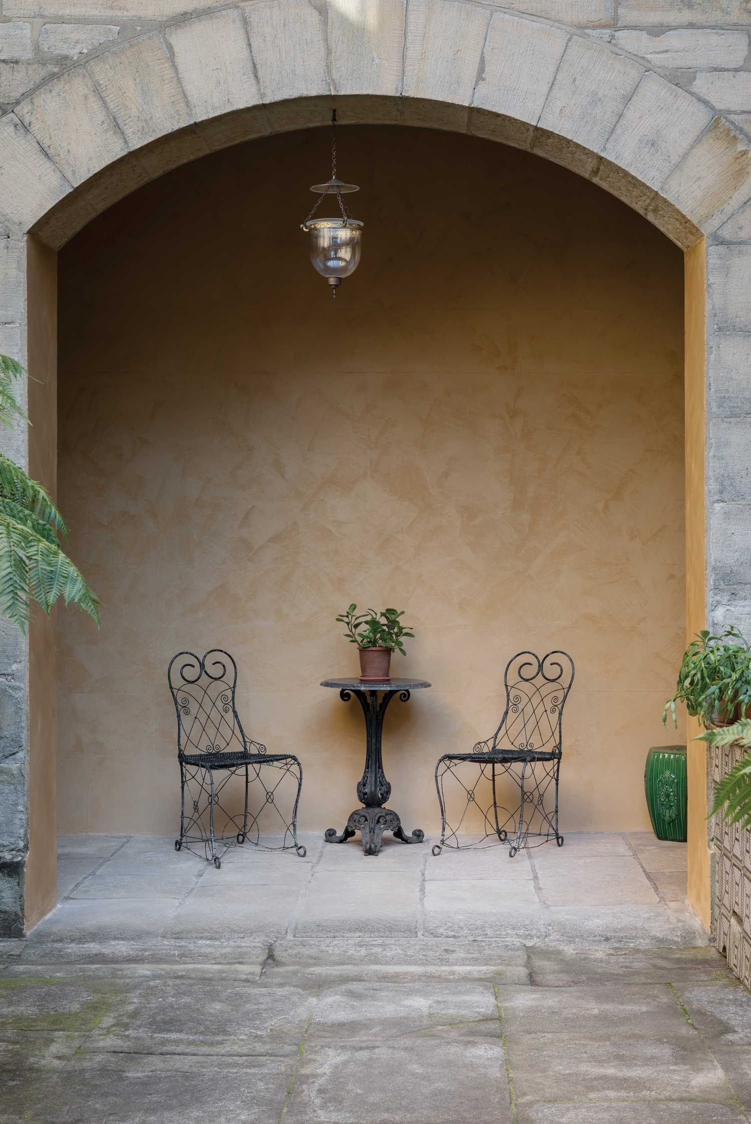 Two wrought iron chairs and plant holder in archway of colonnade.