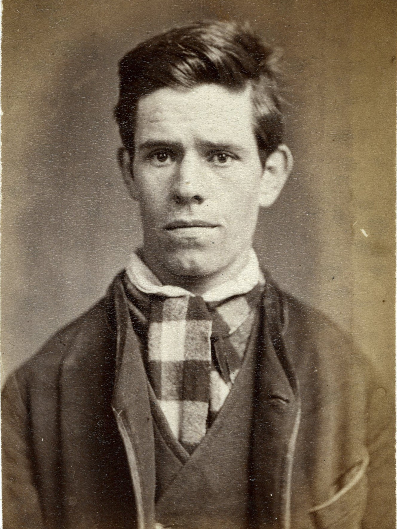 Portrait of young man with checkered neck tie.