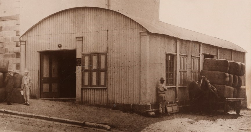 Black and white photo of curved roof building with two men standing to left of doorway.