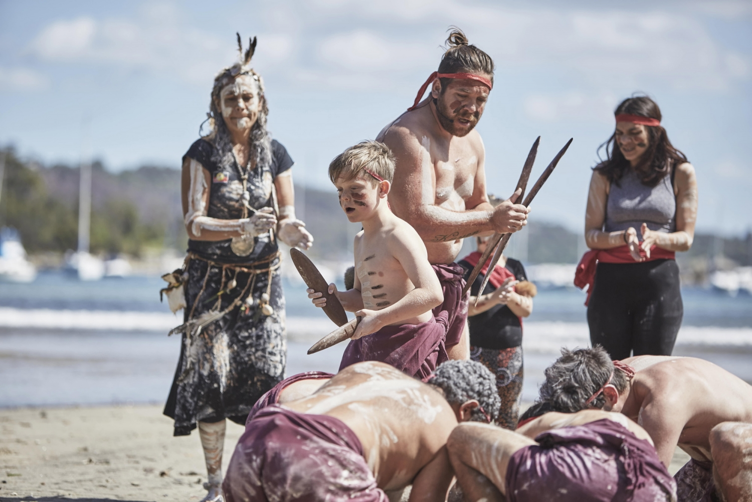 Indigenous dancers in traditional costume dancing on beach with harbour in background.