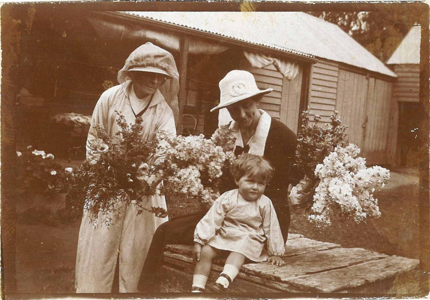 Black and white photo of two women wearing hats, holding flowers on table with small girl seated.
