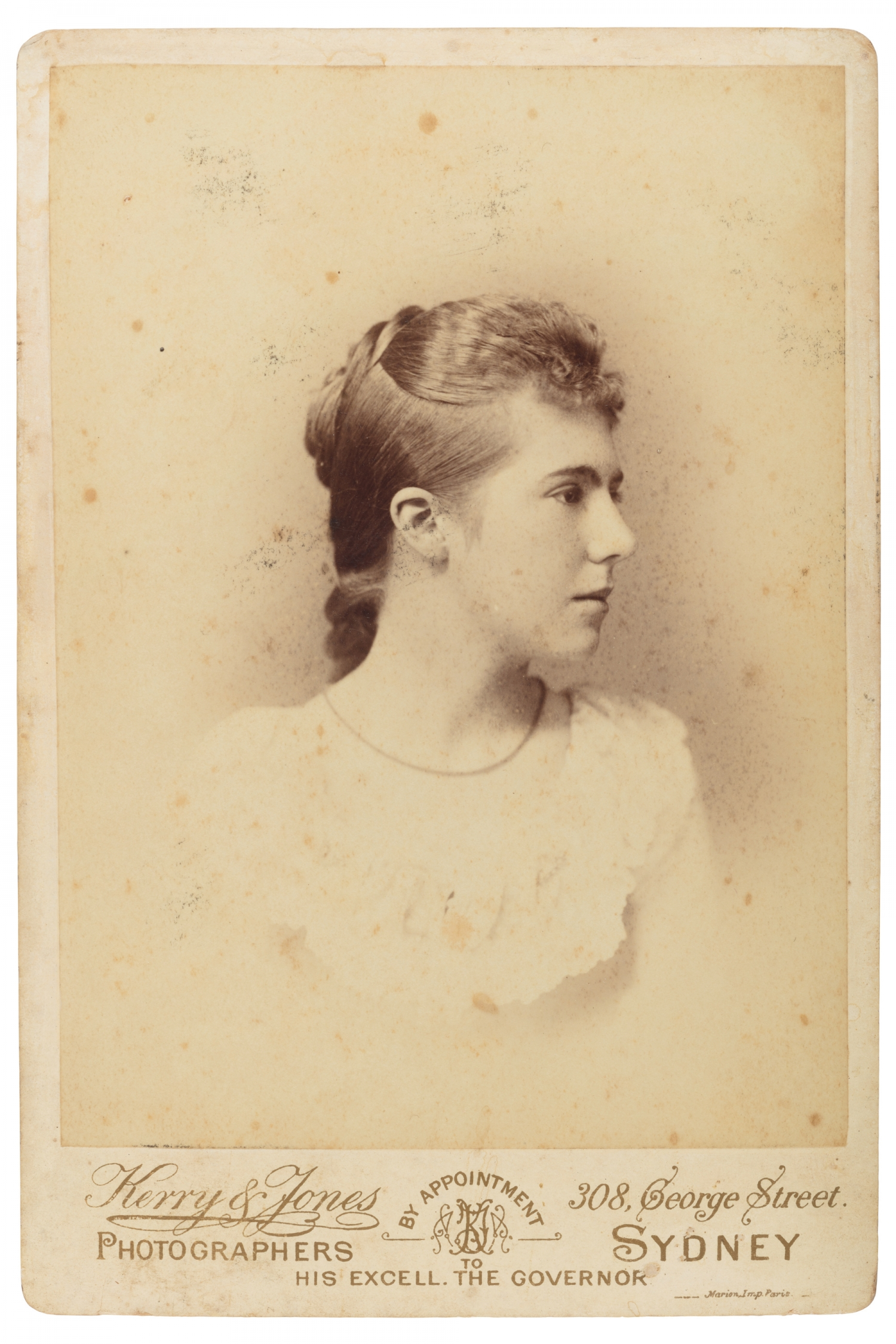 Sepia toned photograph of woman with head turned to right.